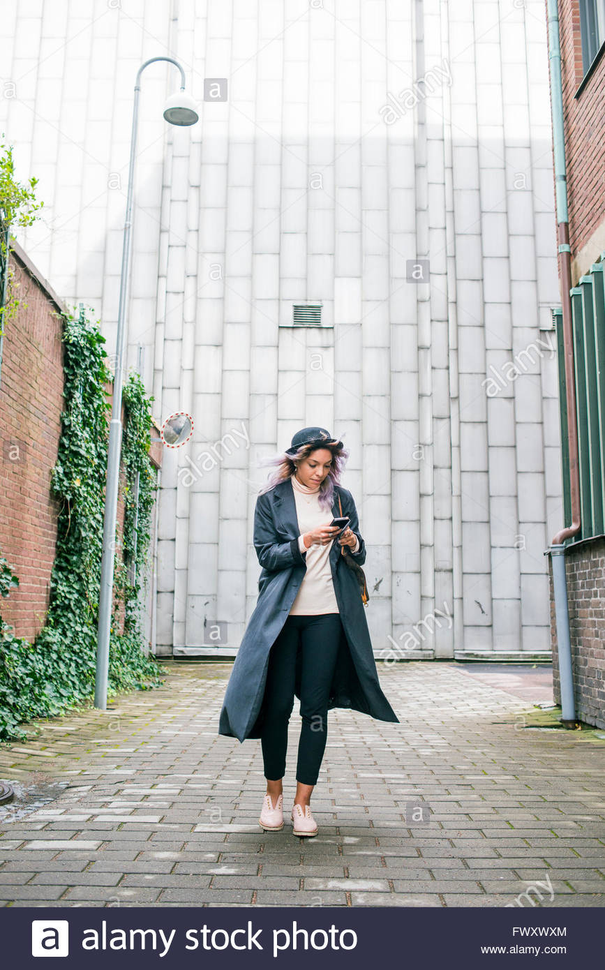 Sweden, Vastra Gotaland, Young woman wearing long overcoat and bowler hat using smart phone - Stock Image