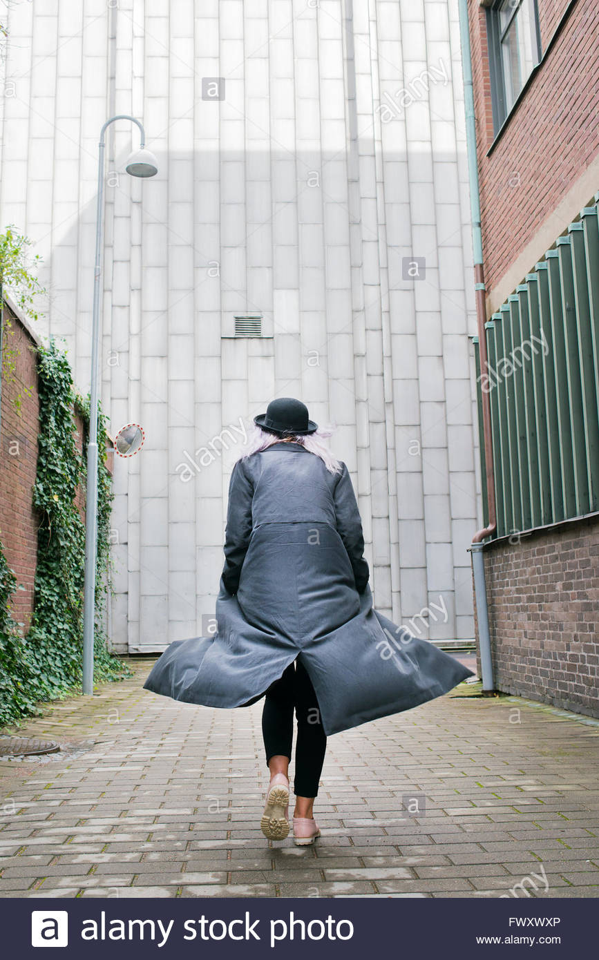 Sweden, Vastra Gotaland, Young woman wearing long overcoat walking away - Stock Image