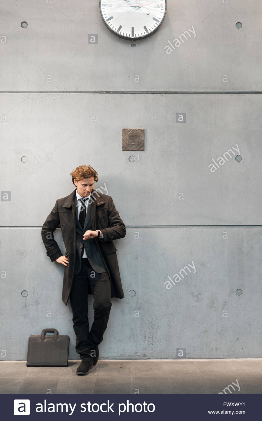 Sweden, Skane, Malmo, Businessman checking time on railroad station platform - Stock Image