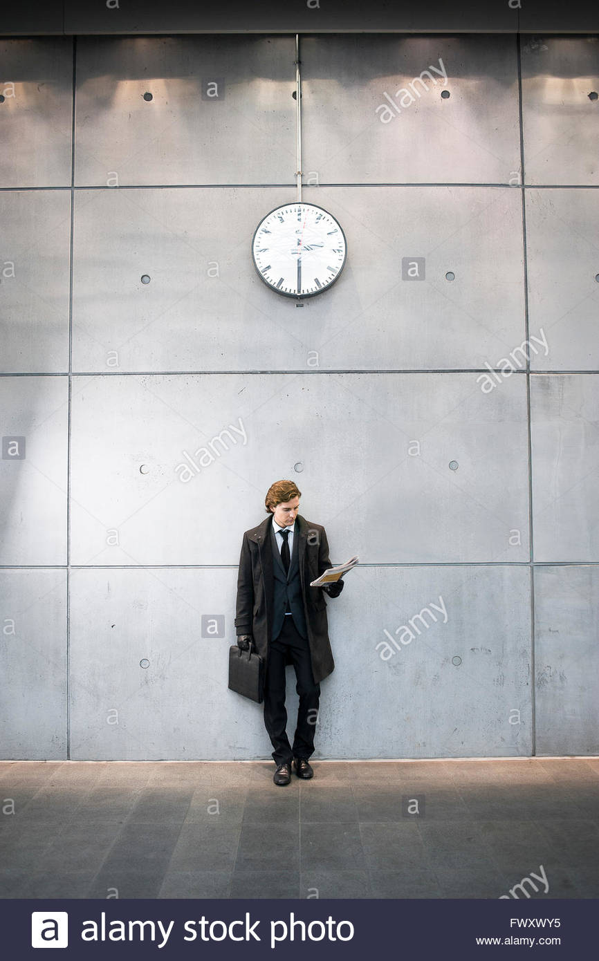 Sweden, Skane, Malmo, Businessman reading newspaper at railroad station - Stock Image