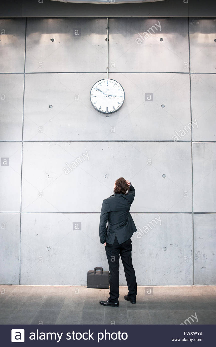 Sweden, Skane, Malmo, Businessman checking time at railroad station - Stock Image