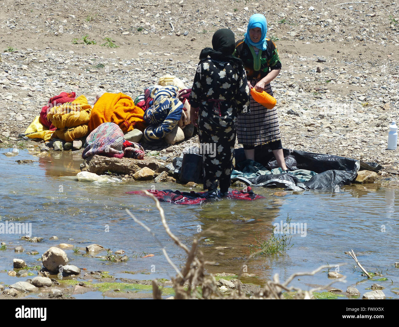 Women wash clothes in a river, Morocco - Stock Image