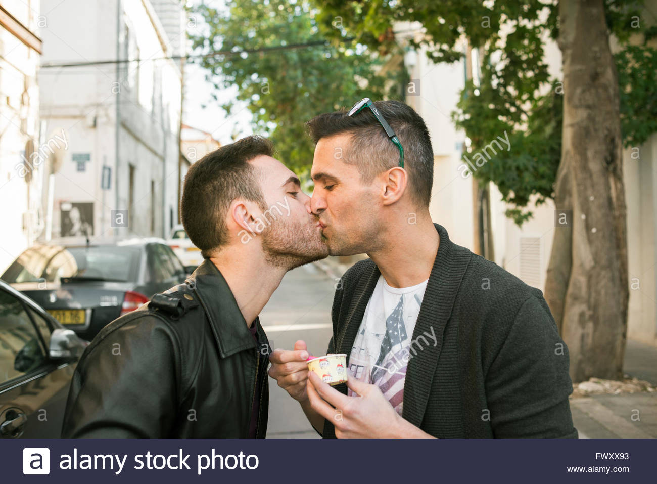 Israel, Tel Aviv, Homosexual couple kissing in street - Stock Image