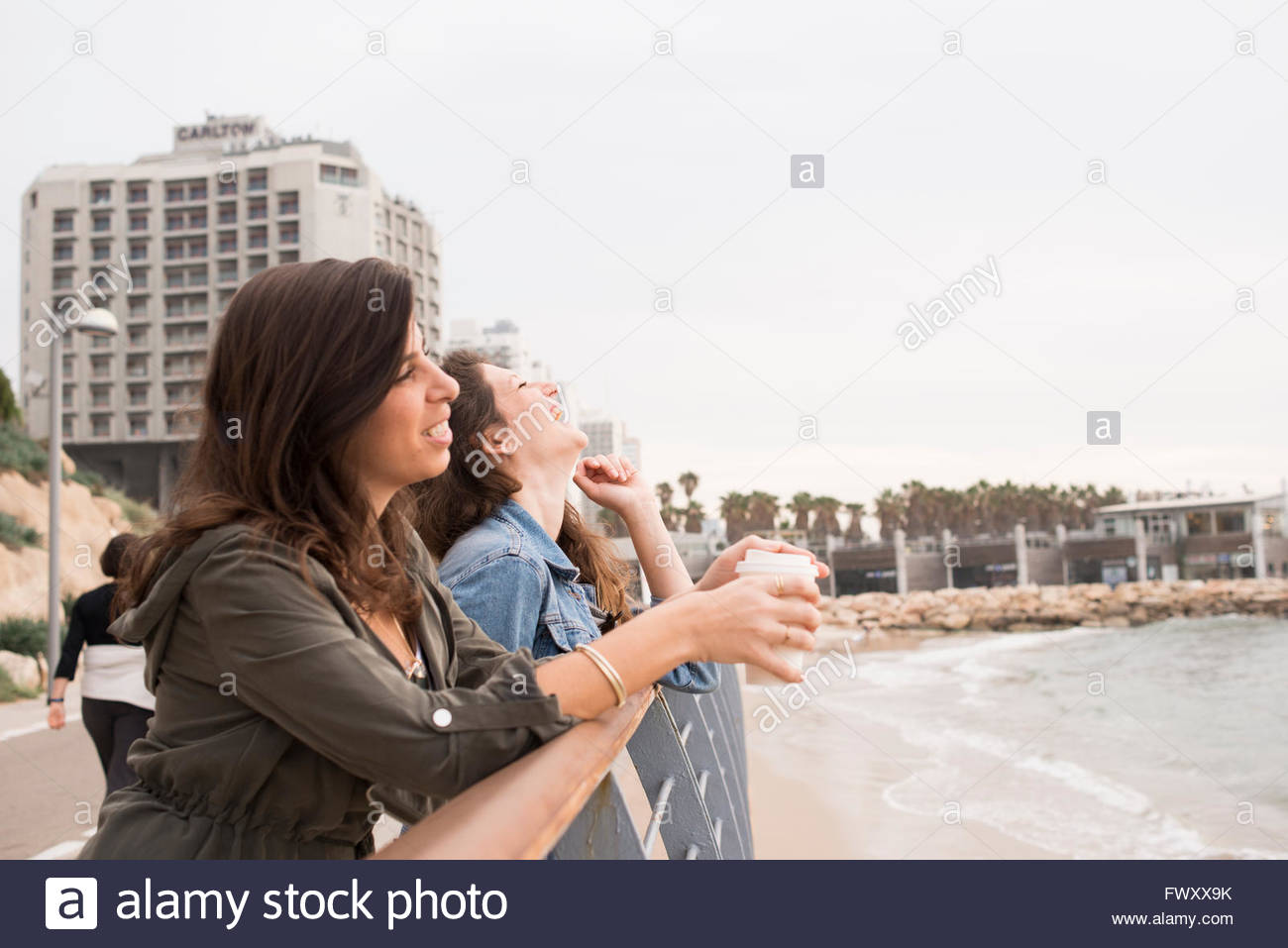 Israel, Tel Aviv, Two women standing by railing of promenade - Stock Image
