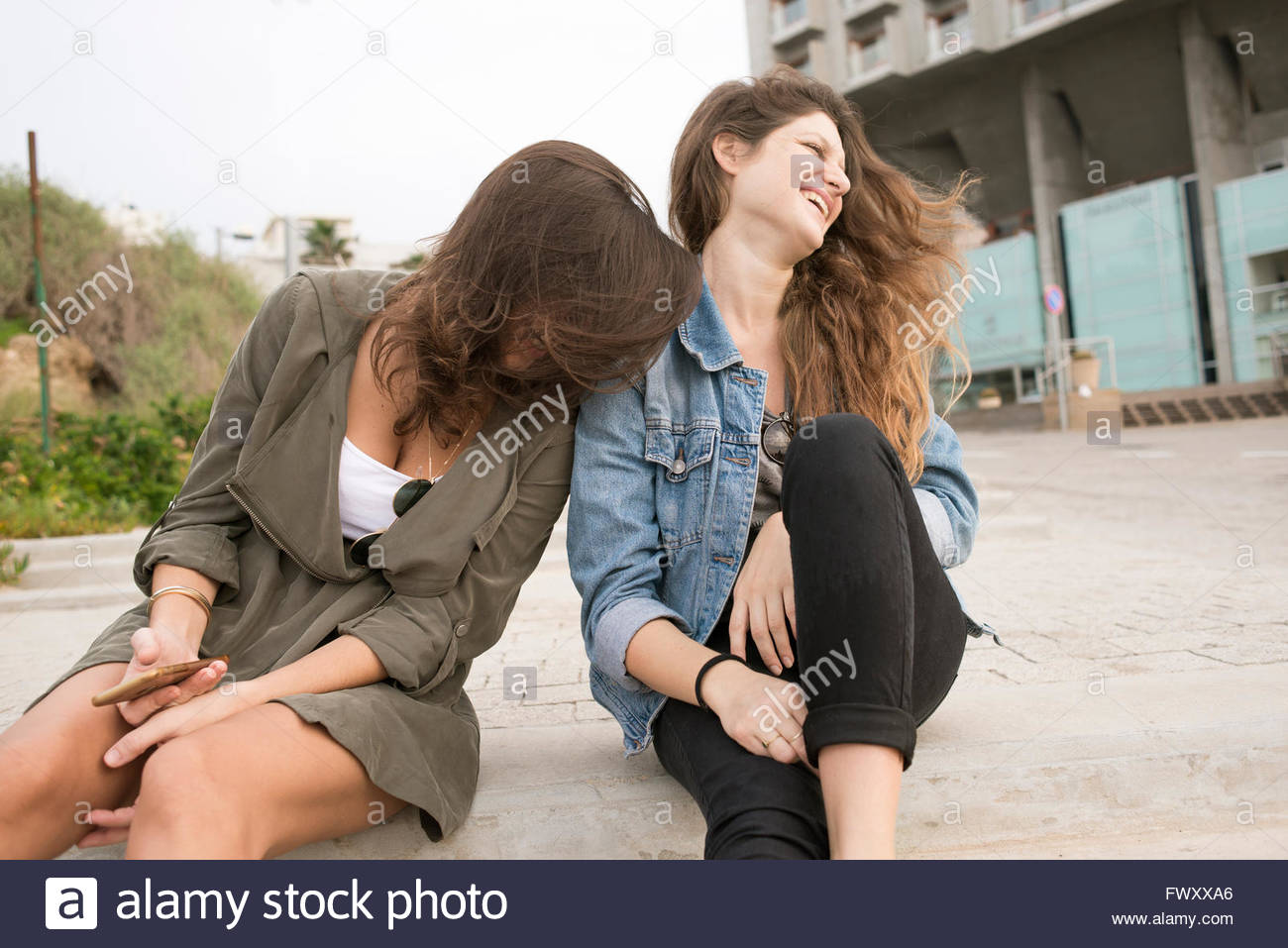 Israel, Tel Aviv, Laughing  young women sitting on steps - Stock Image