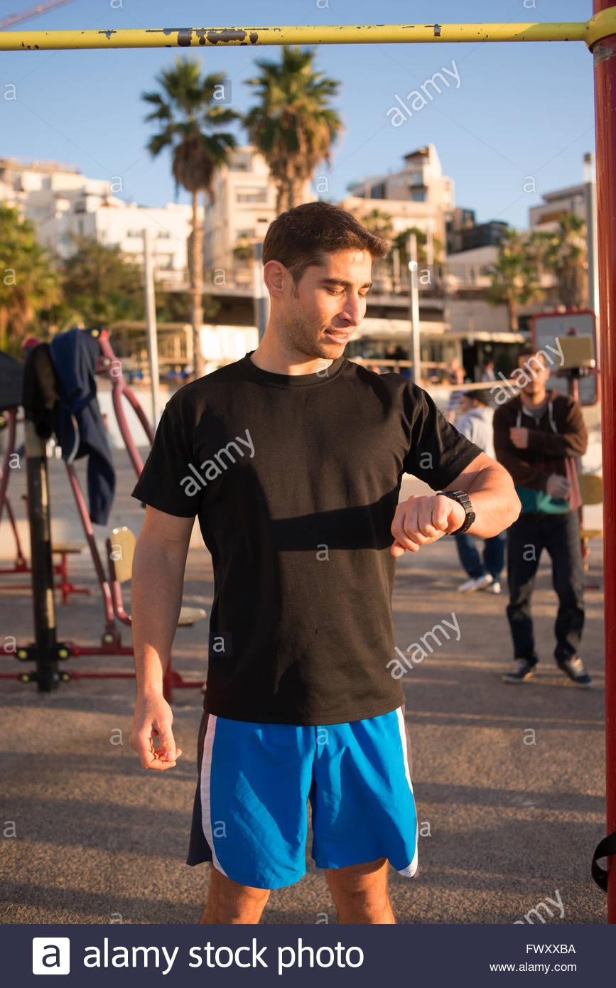 Israel, Tel Aviv, Mid adult man looking at smart watch - Stock Image