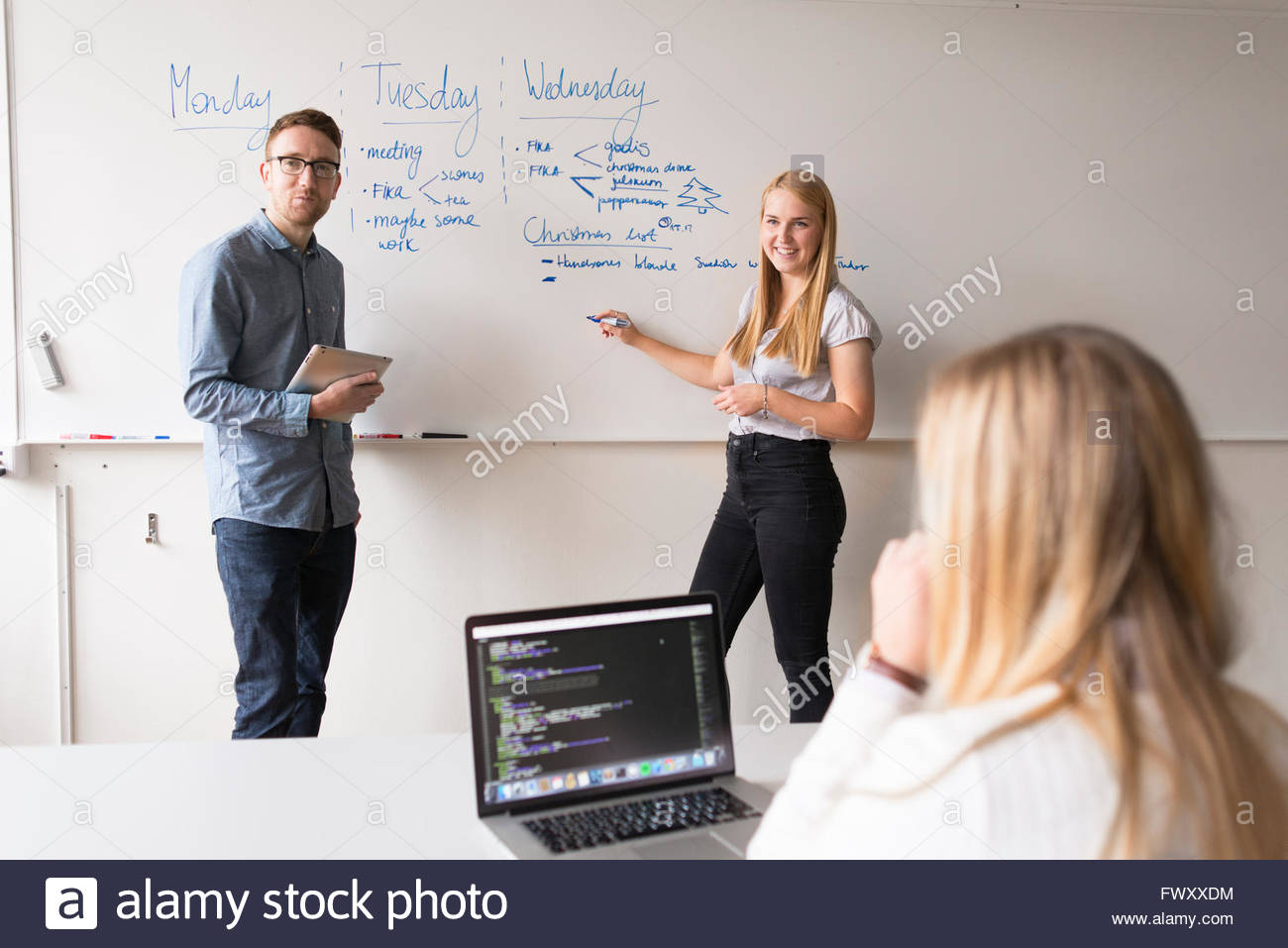 Sweden, Colleagues giving presentation in board room - Stock Image