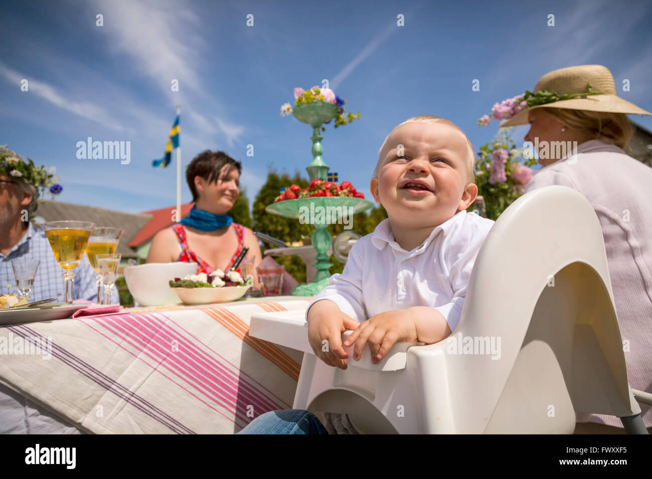 Sweden, Skane, Family with one child (0-1 month) during midsummer celebrations - Stock Image