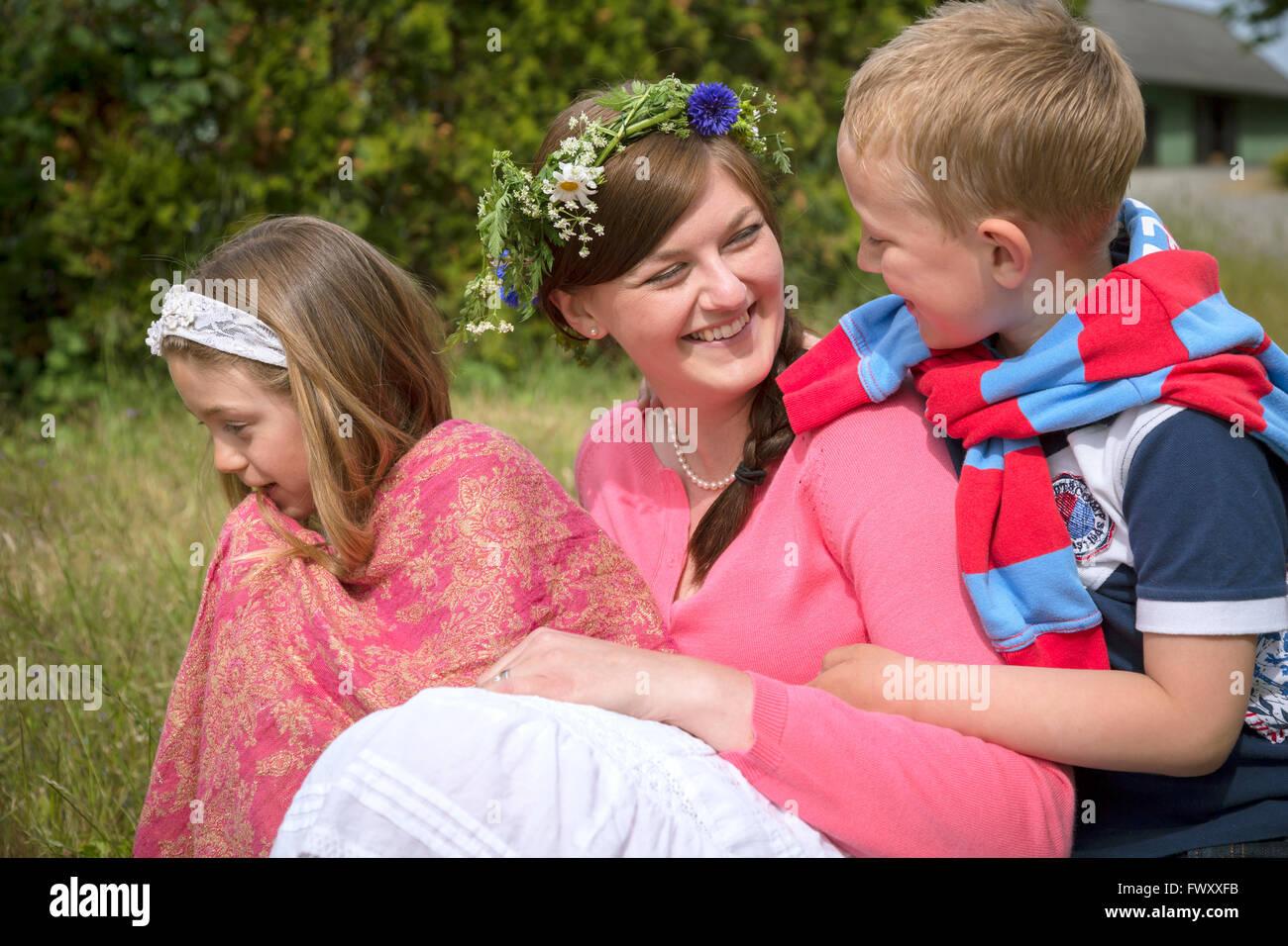 Sweden, Skane, Mother with children (6-7, 8-9) during midsummer celebrations - Stock Image