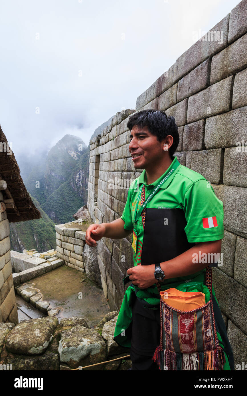 A group of tourists with local guide explore the Old ruins of  Machu Picchu, Cuzco, Peru - Stock Image