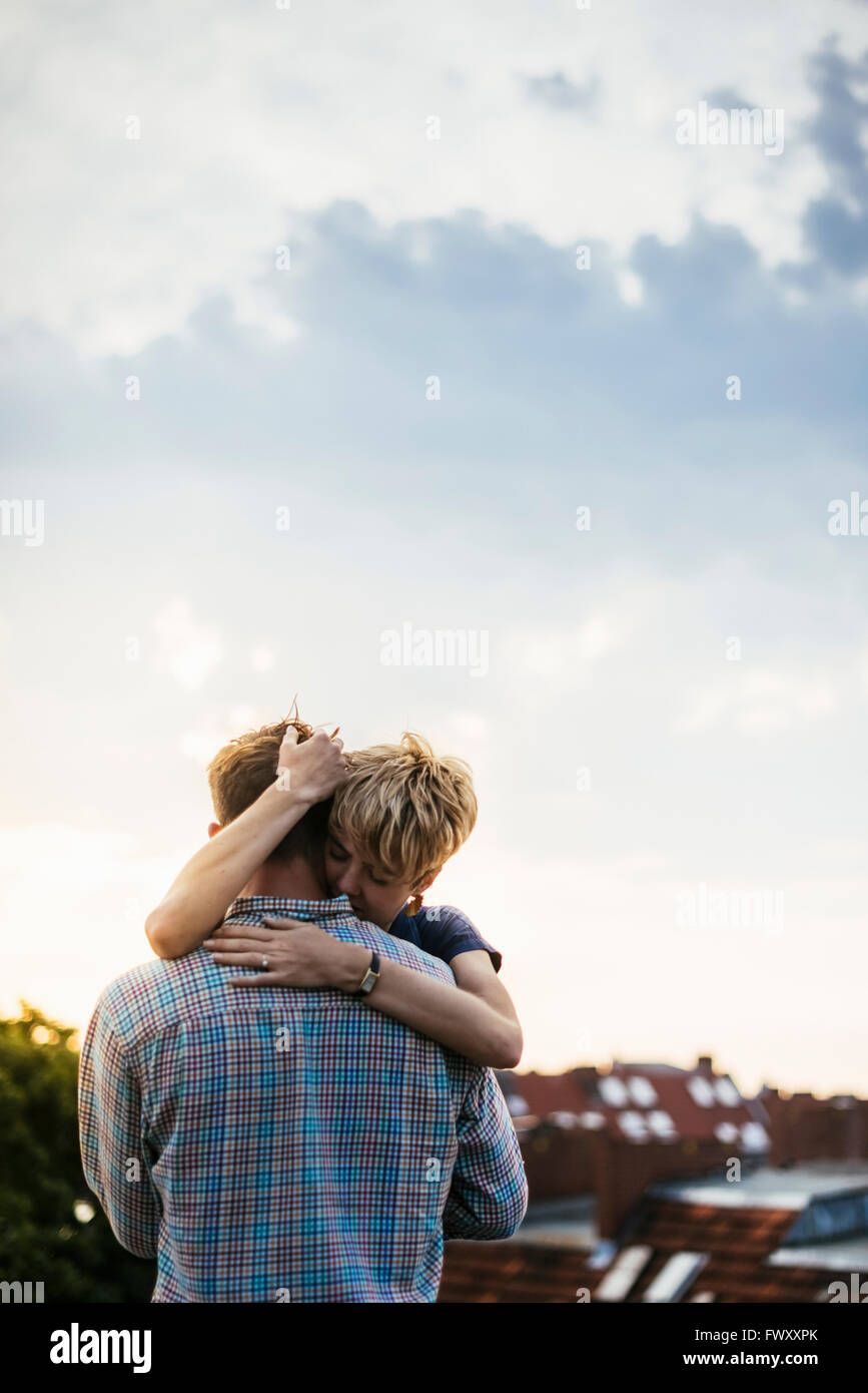 Germany, Berlin, Young couple hugging on rooftop at sunset - Stock Image