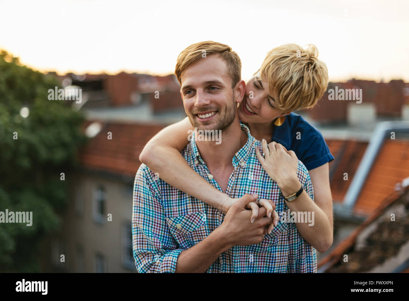 Germany, Berlin, Young couple hugging on rooftop at sunset Stock Photo