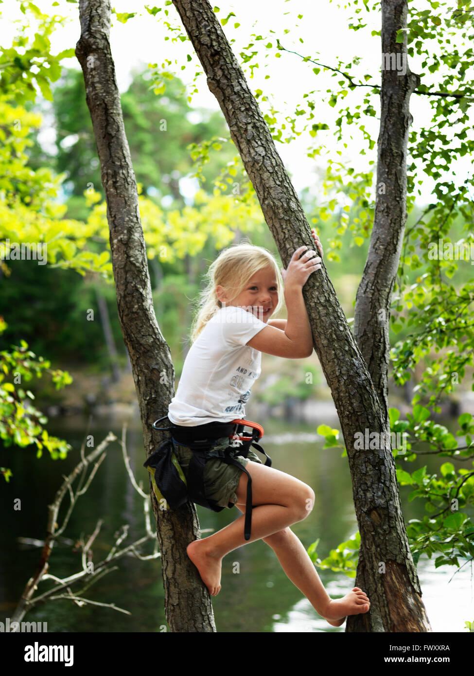 Sweden, Ostergotland, Agelsjon, Smiling girl (8-9) climbing tree - Stock Image
