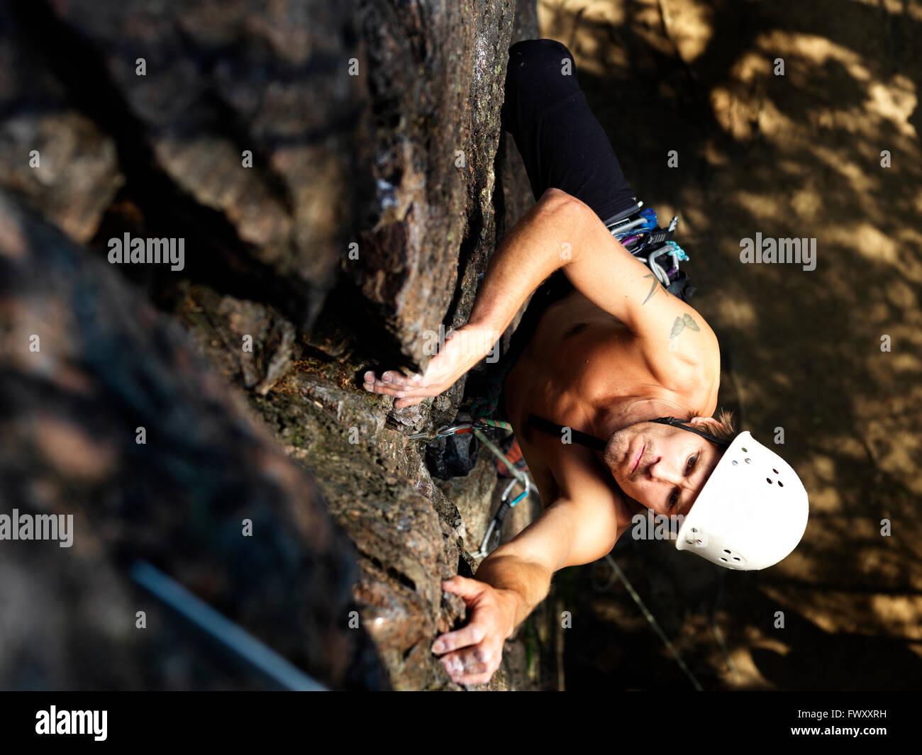 Sweden, Ostergotland, Agelsjon, Man climbing rock - Stock Image