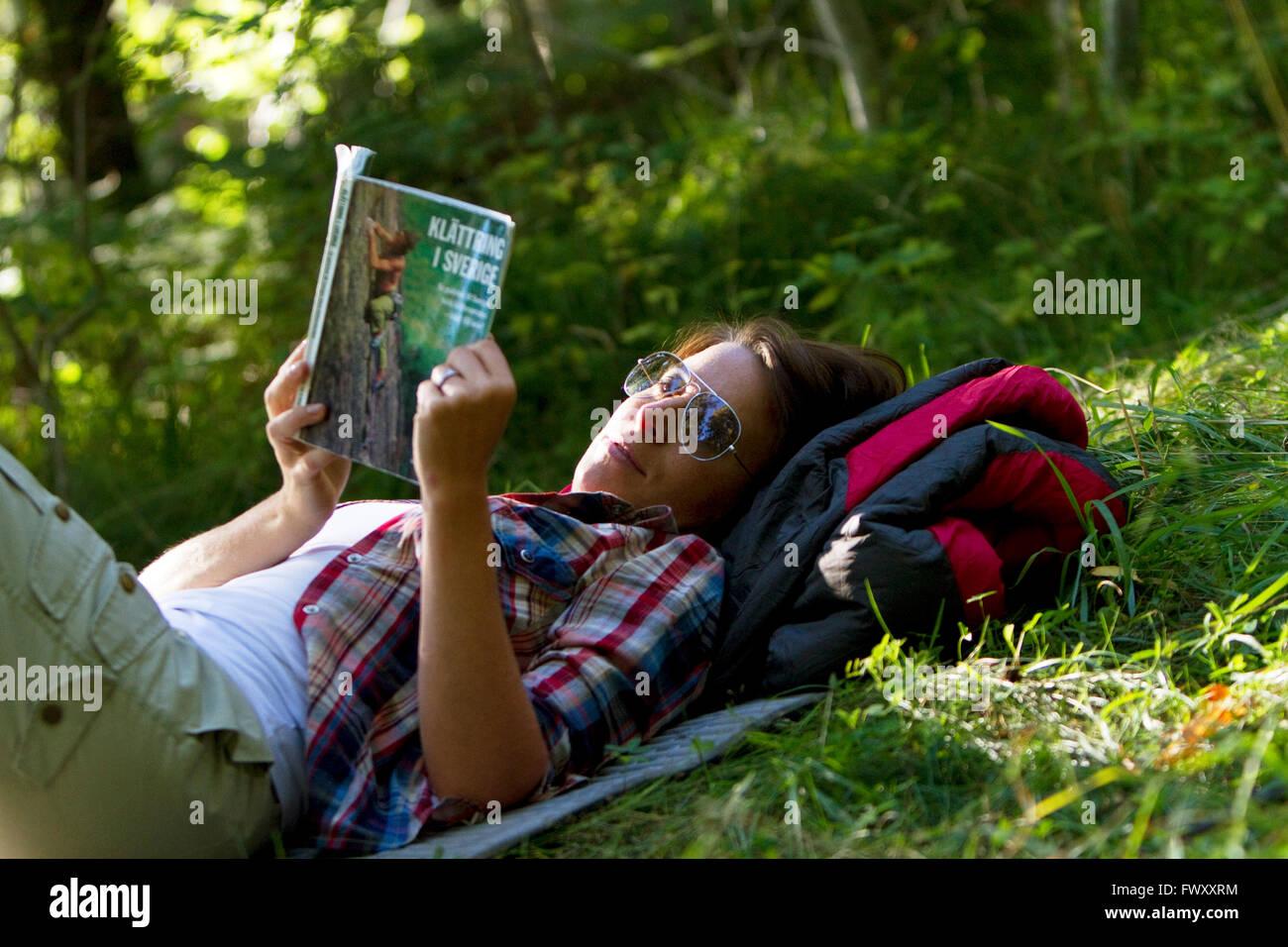 Sweden, Ostergotland, Agelsjon, Female hiker lying on grass and reading guidebook - Stock Image