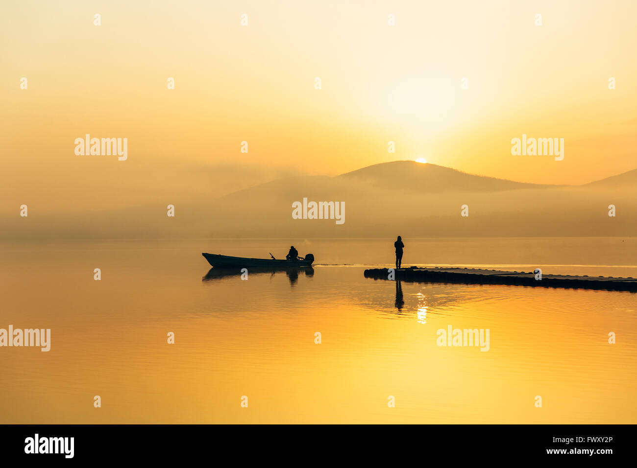 Japan, Izu Peninsula, Silhouettes of two people in boat and on jetty - Stock Image