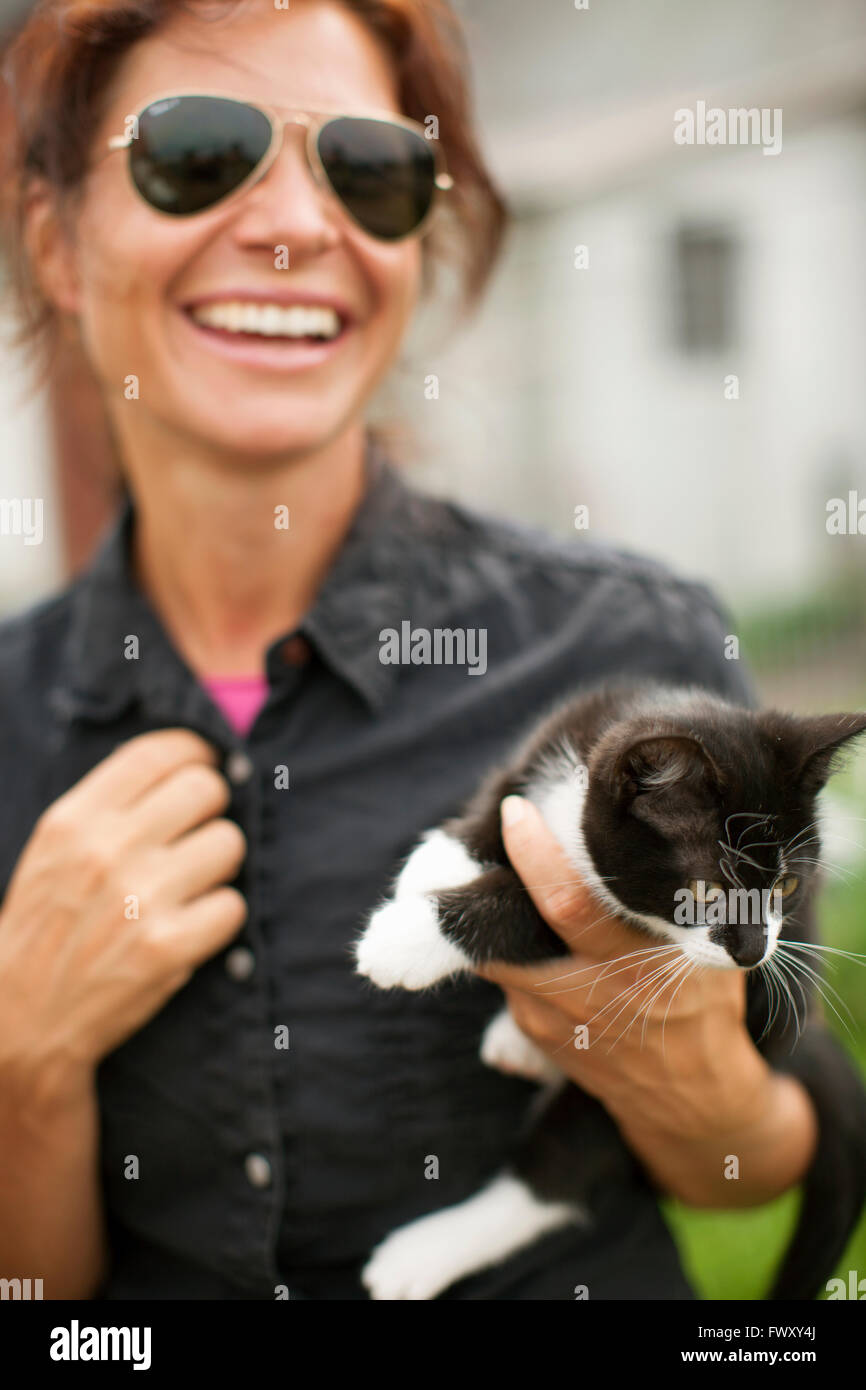 Sweden, Skane, Woman holding cat and laughing - Stock Image