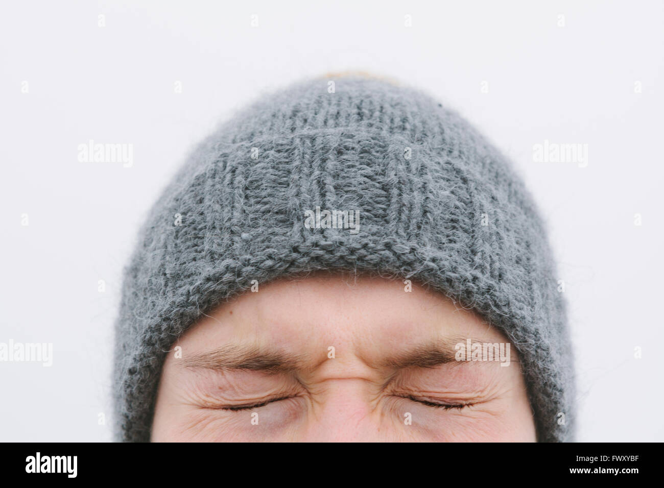 Finland, Helsingfors, High section shot of young man's face with eyes closed tight - Stock Image