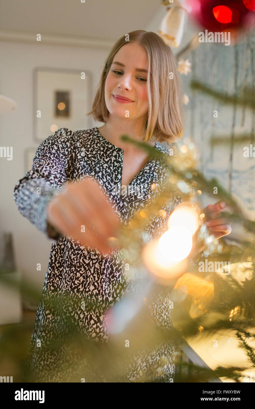 Finland, Young woman decorating Christmas tree - Stock Image