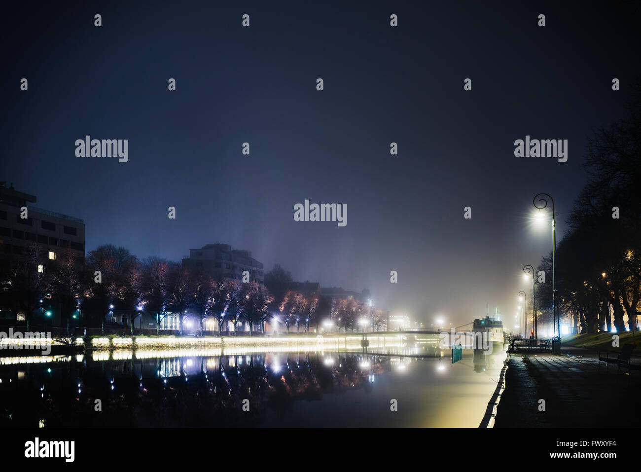 Finland, Varsinais-Suomi, Turku, Illuminated riverbank at night - Stock Image