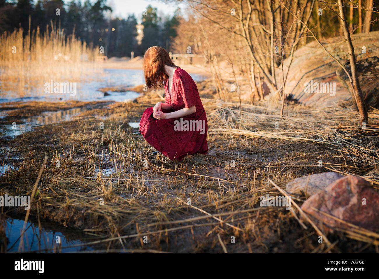 Finland, Varsinais-Suomi, Young woman crouching in wetlands Stock Photo