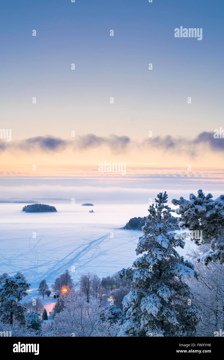 Finland, Pirkanmaa, Tampere, Landscape with frozen lake at dusk - Stock Image
