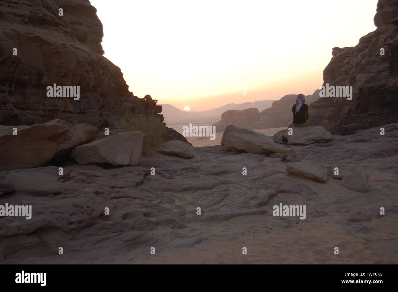 Bedouin man watching the sunrise in Wadi Rum, Jordan - Stock Image