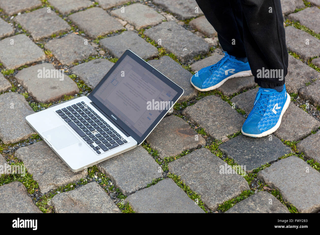 Notebook lying on the ground and legs in sport shoes, low section - Stock Image