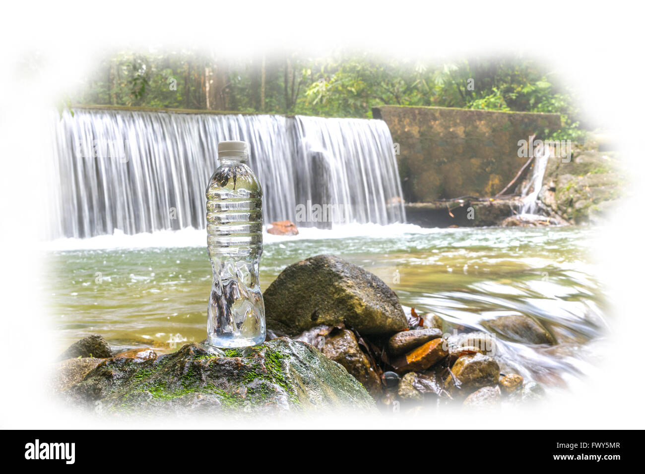 Plastic bottle with waterfall background at tropical forest - Stock Image