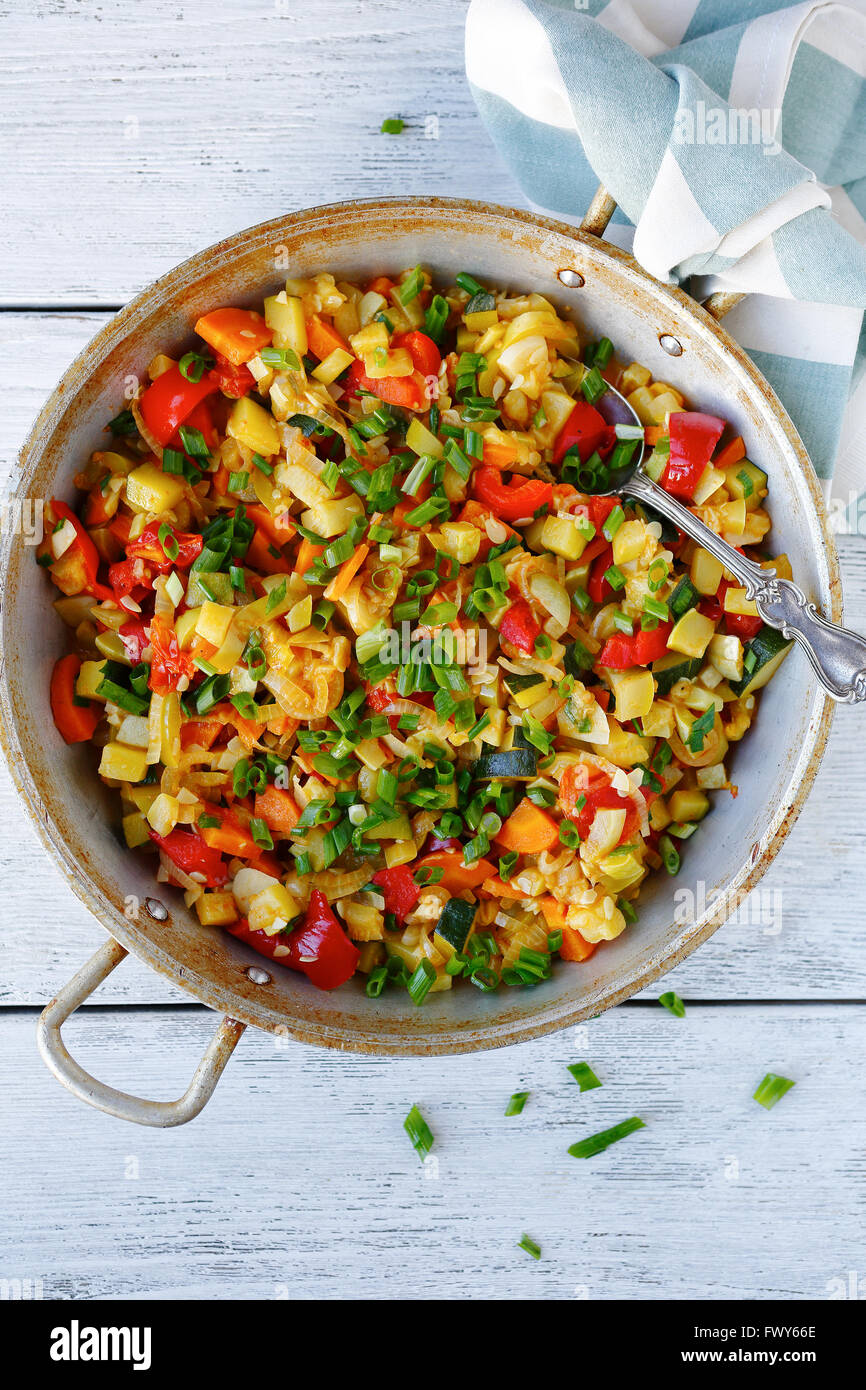stewed pieces of vegetables in a frying pan, above summer food Stock Photo