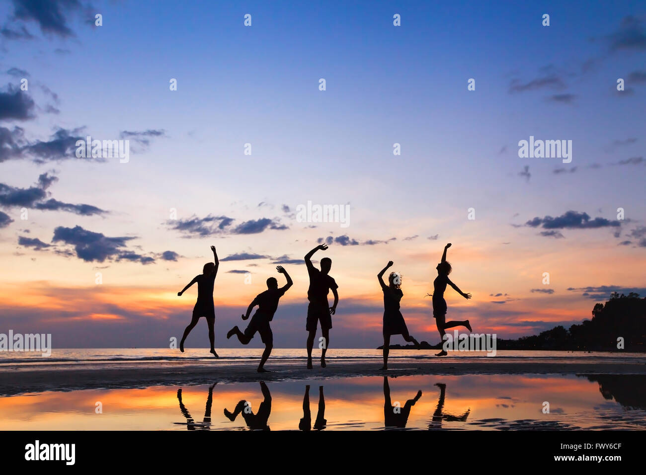 group of people jumping on the beach at sunset, silhouette of friends having fun together Stock Photo