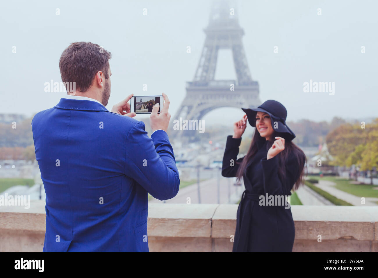 mobile photography, man taking photo of woman with his phone, couple of tourists near Eiffel Tower in Paris, France - Stock Image