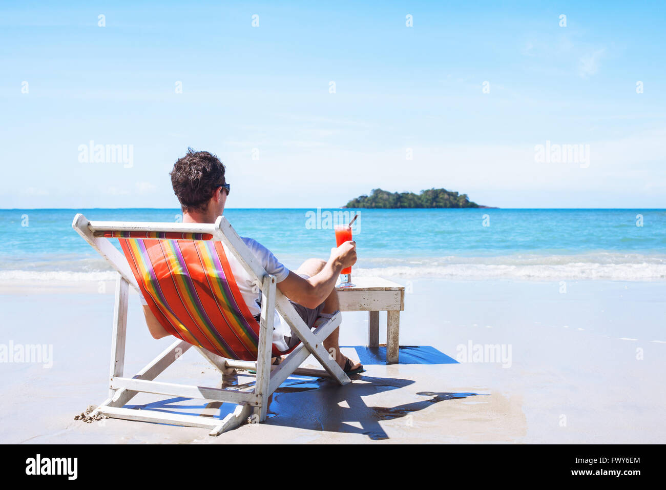 man relaxing on private beach on paradise island, luxurious holidays, tourist with cocktail sitting near the sea - Stock Image