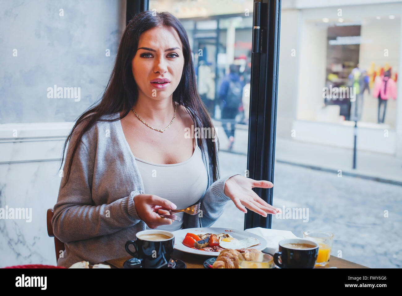 unhappy customer in restaurant, angry woman complaining about food and service in cafe - Stock Image