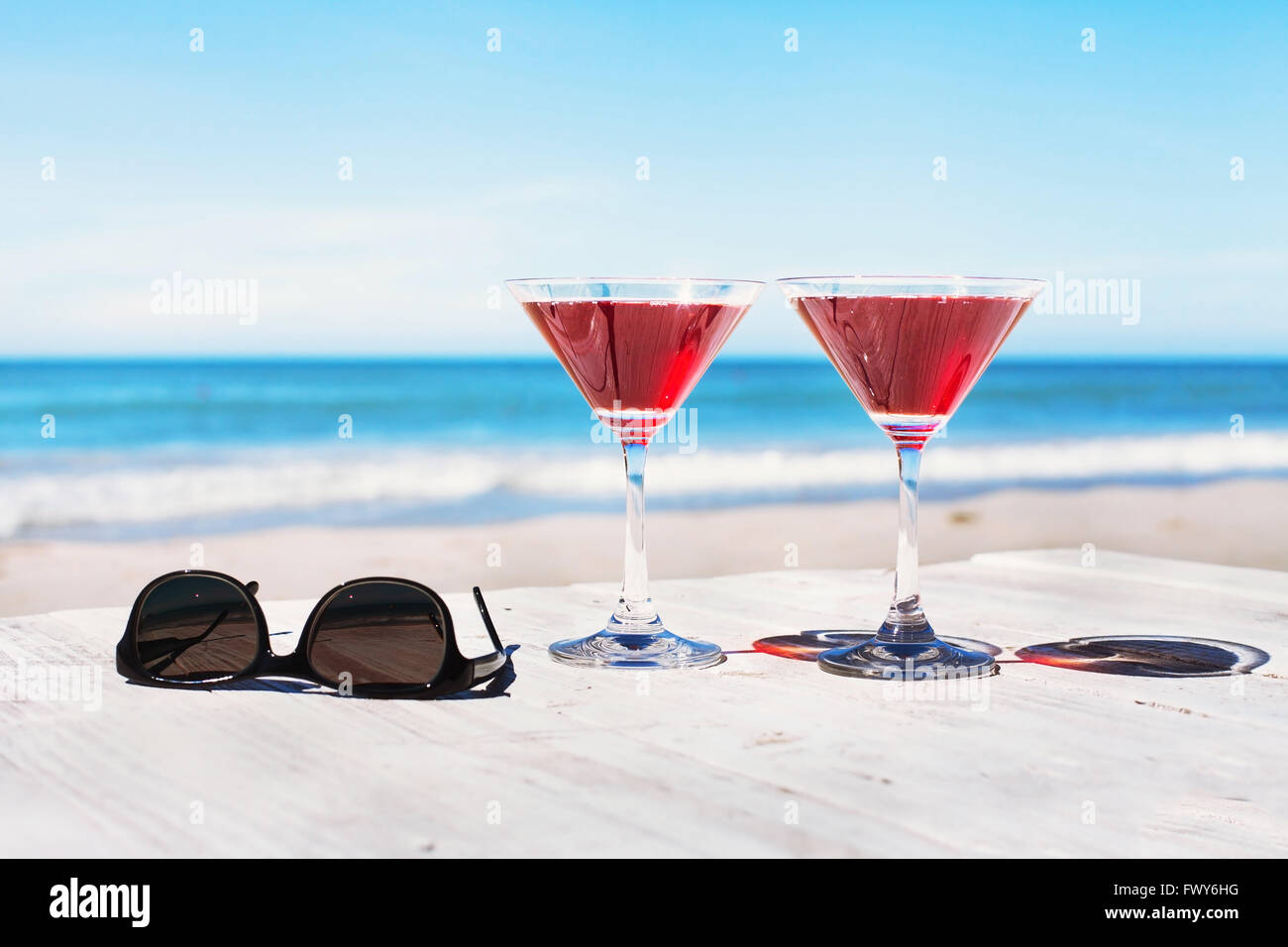 summer holidays concept, two cocktails and sunglasses on the beach table, tropical vacations - Stock Image