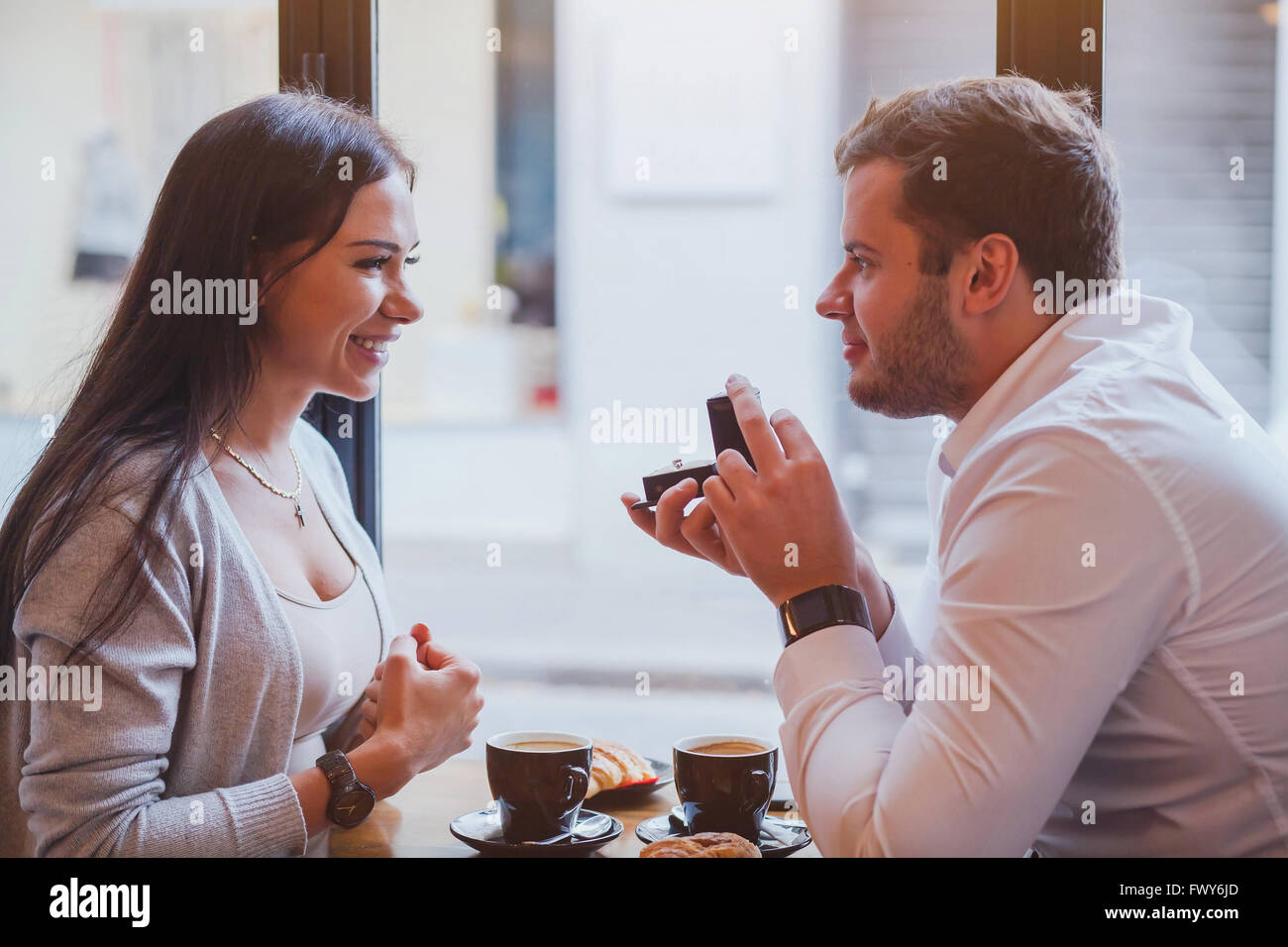 proposal, engagement concept, happy couple in restaurant, man offers the ring, marry me - Stock Image