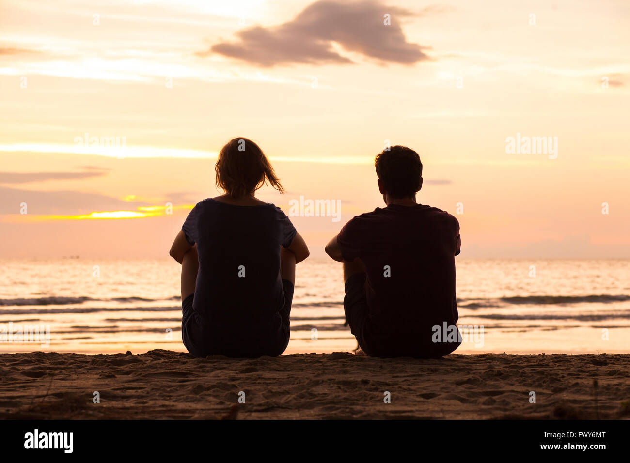 friends sitting together on the beach and watching sunset, friendship concept - Stock Image