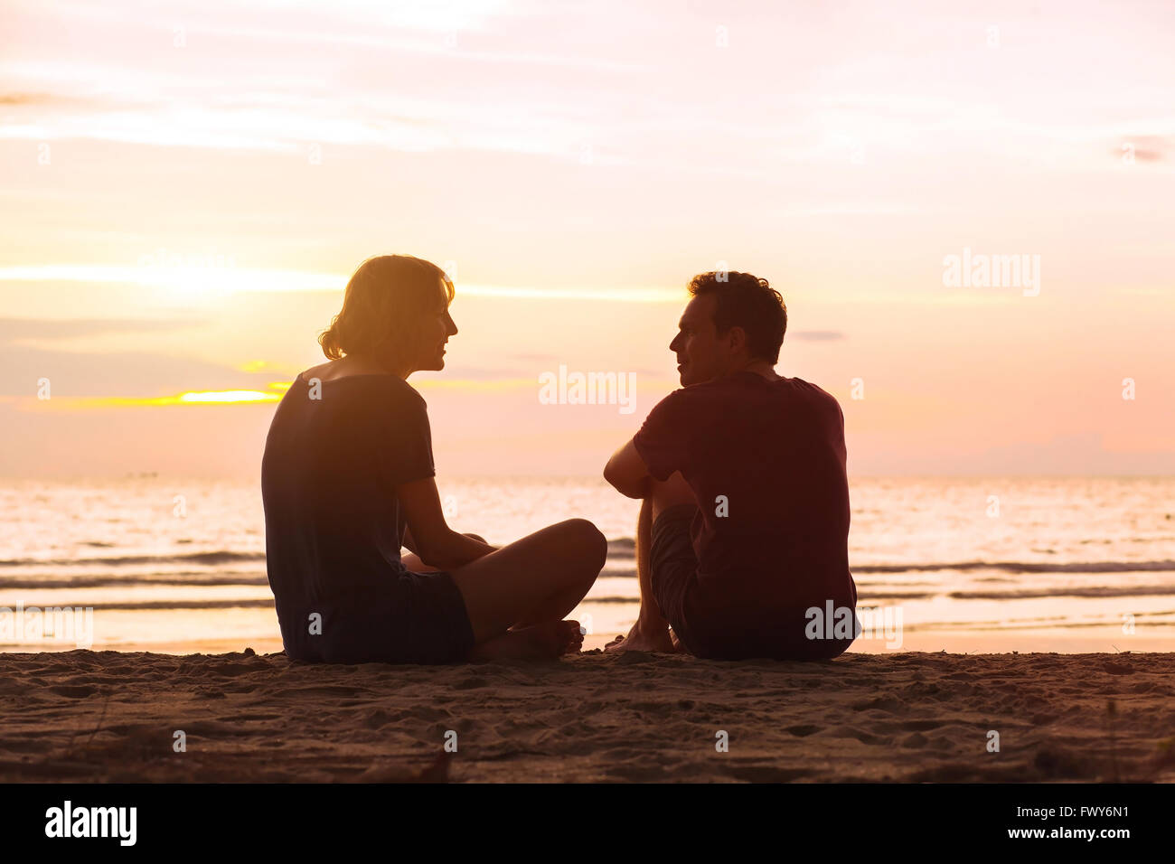 man and woman on the beach at sunset, young couple talking near the sea, dating or friendship concept - Stock Image