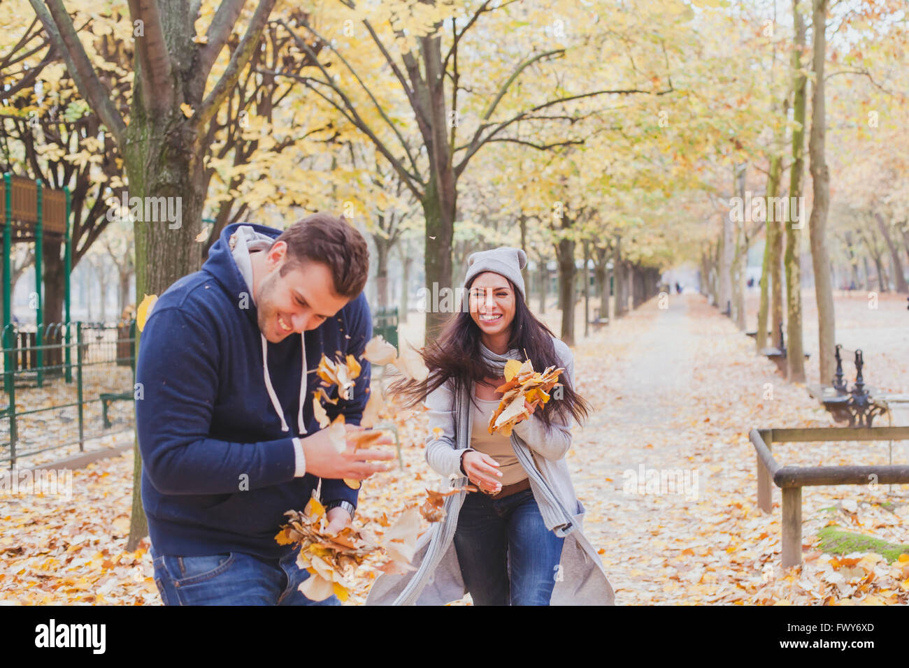 happy young couple playing and laughing together in autumn park Stock Photo