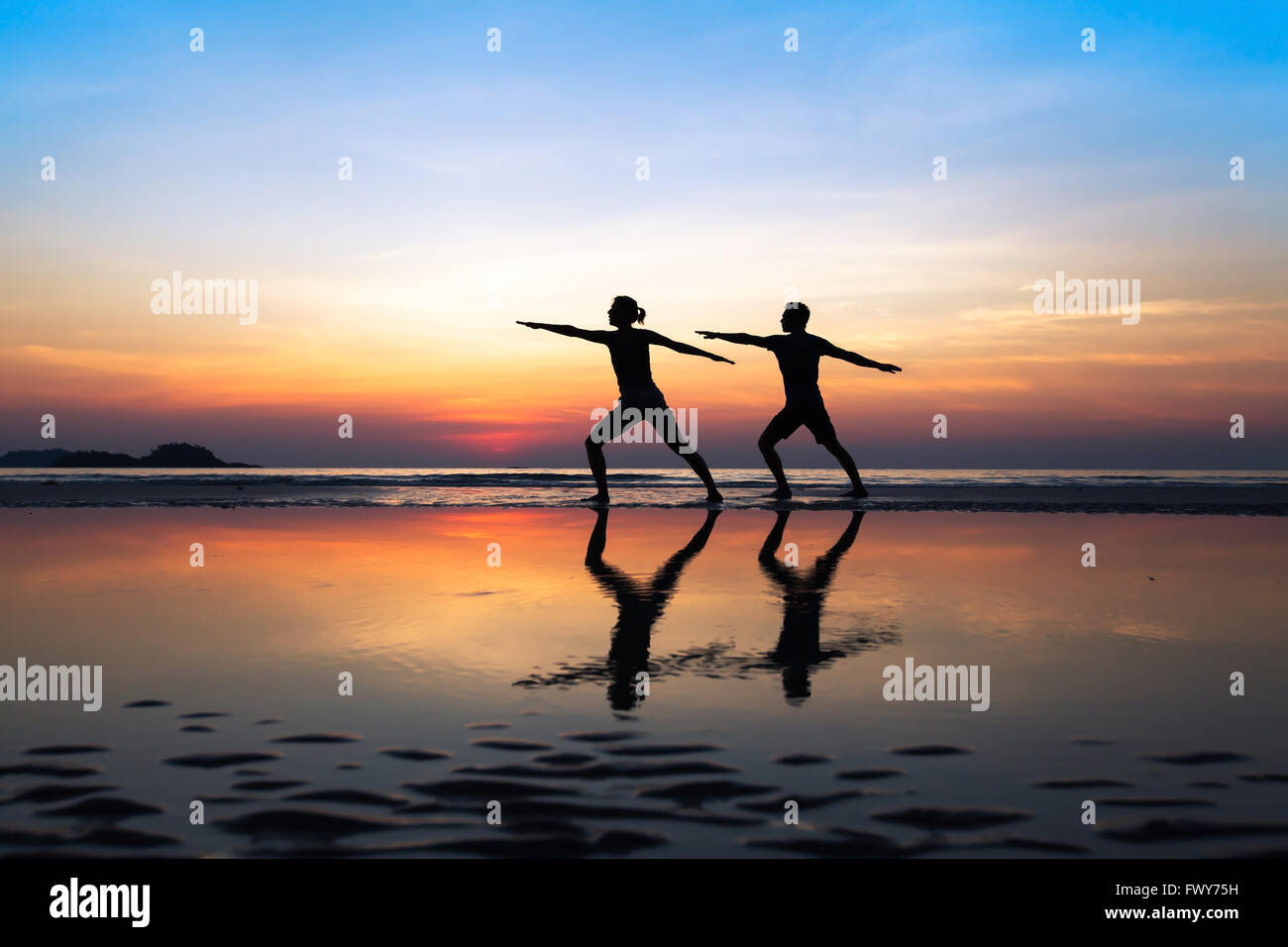 group of people practicing yoga, couple doing stretchings on the beach at sunset - Stock Image