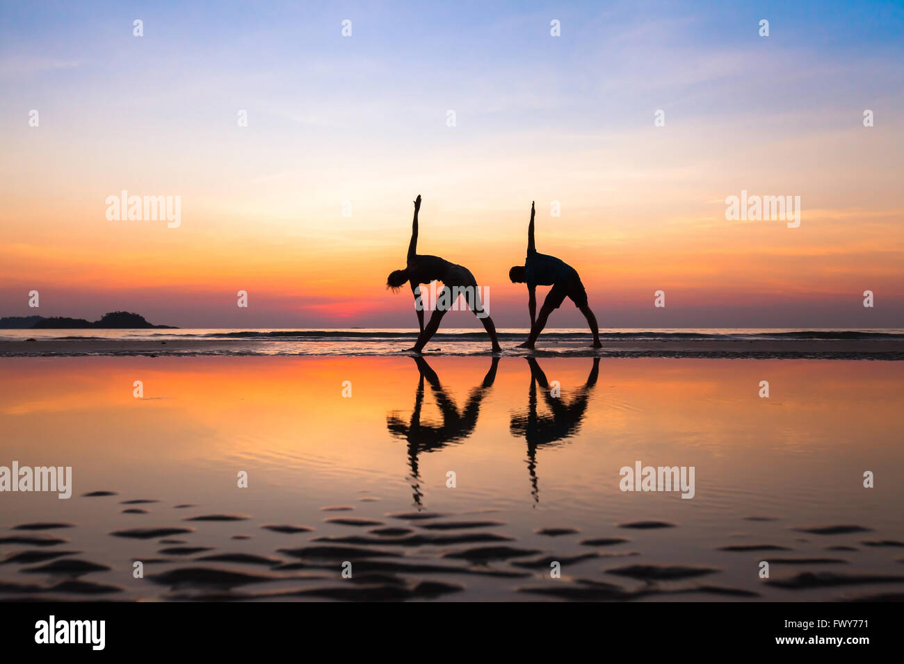 stretchings on the beach at sunset, yoga exercises, silhouettes of couple - Stock Image