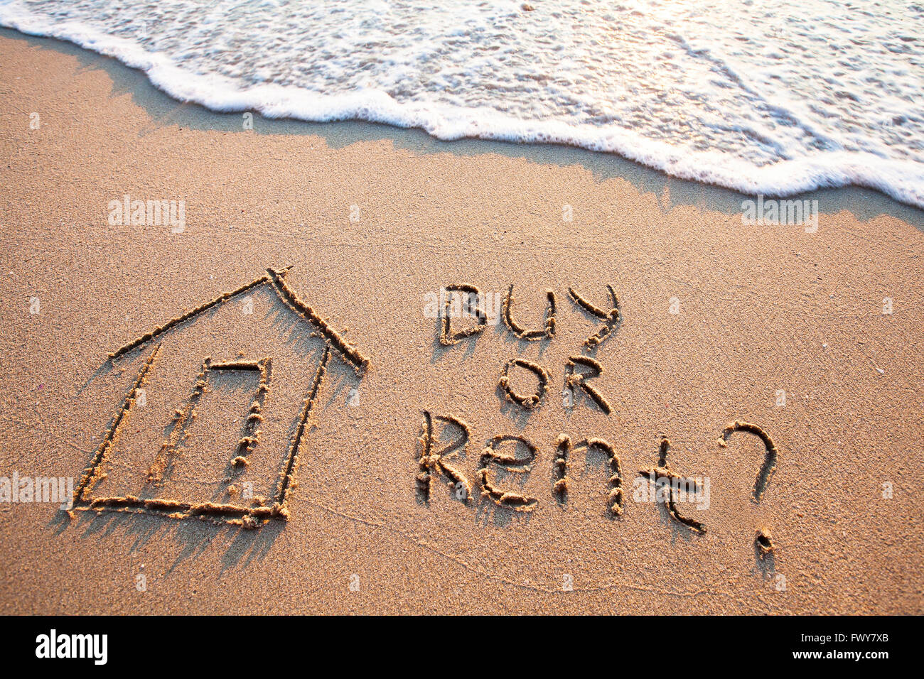 buy or rent concept, text on the sand, real estate - Stock Image