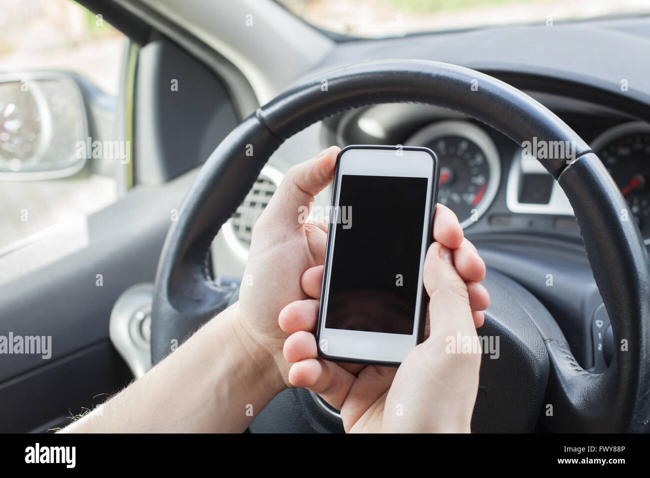 smartphone in the car, male hands holding mobile with empty screen - Stock Image