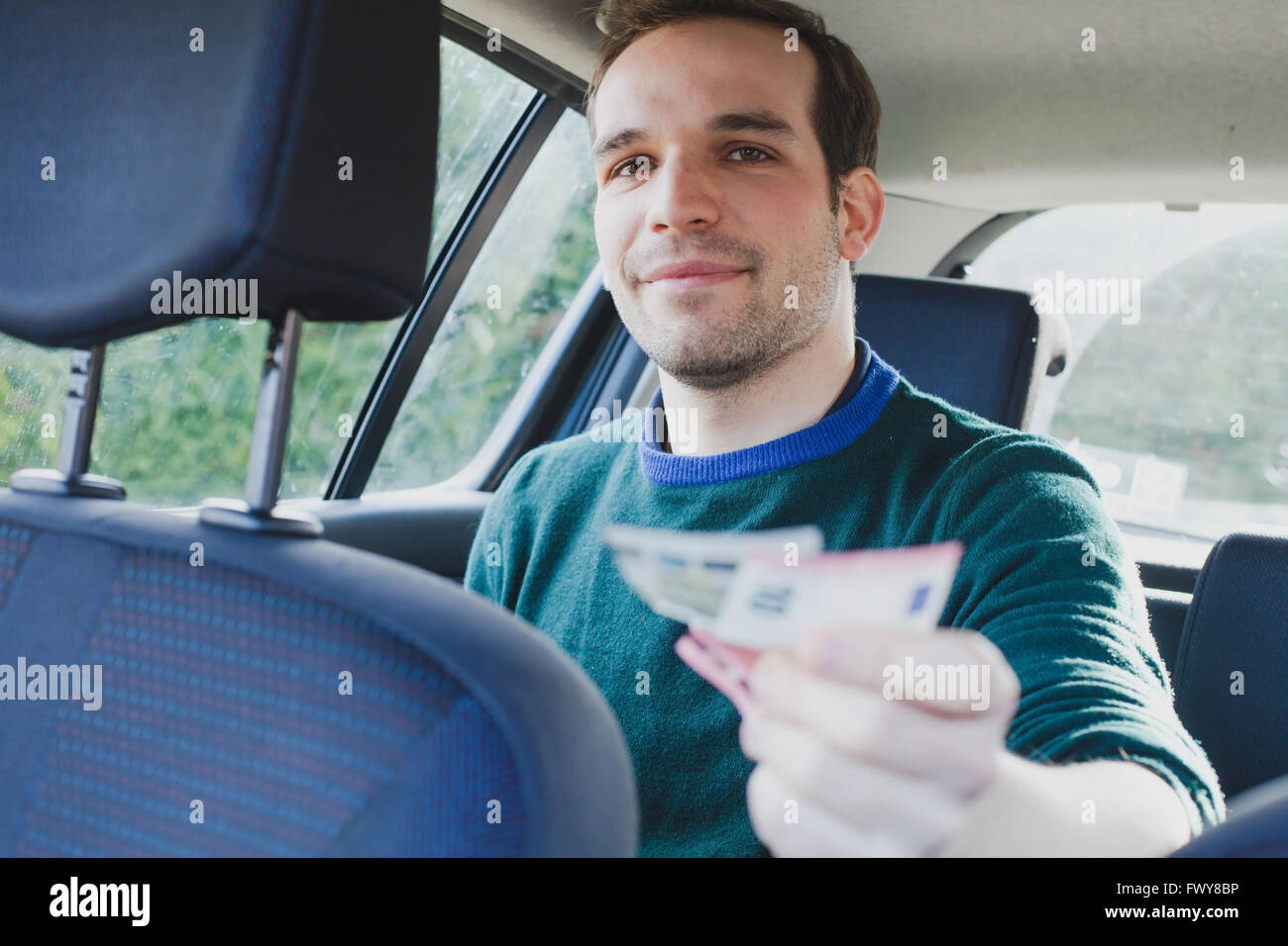 happy passenger in taxi paying by cash - Stock Image