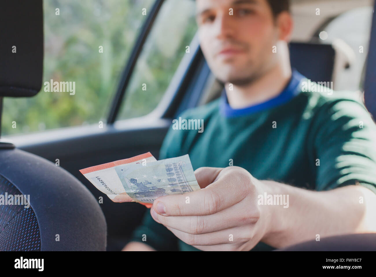 pay by cash in taxi, closeup of hand of passenger giving money to the driver in car - Stock Image