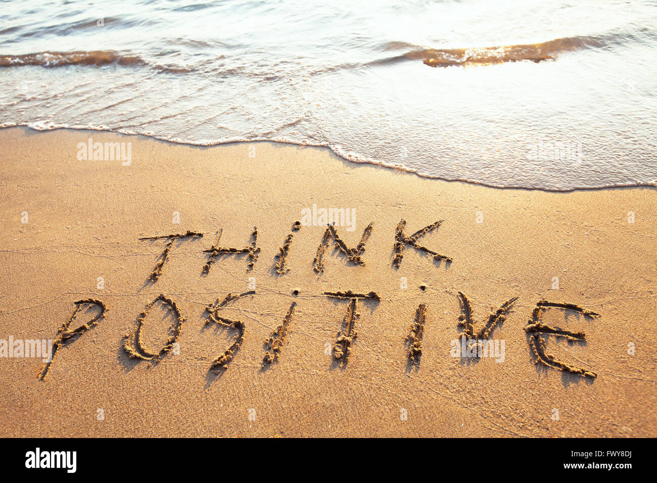 think positive, concept written on the sand Stock Photo