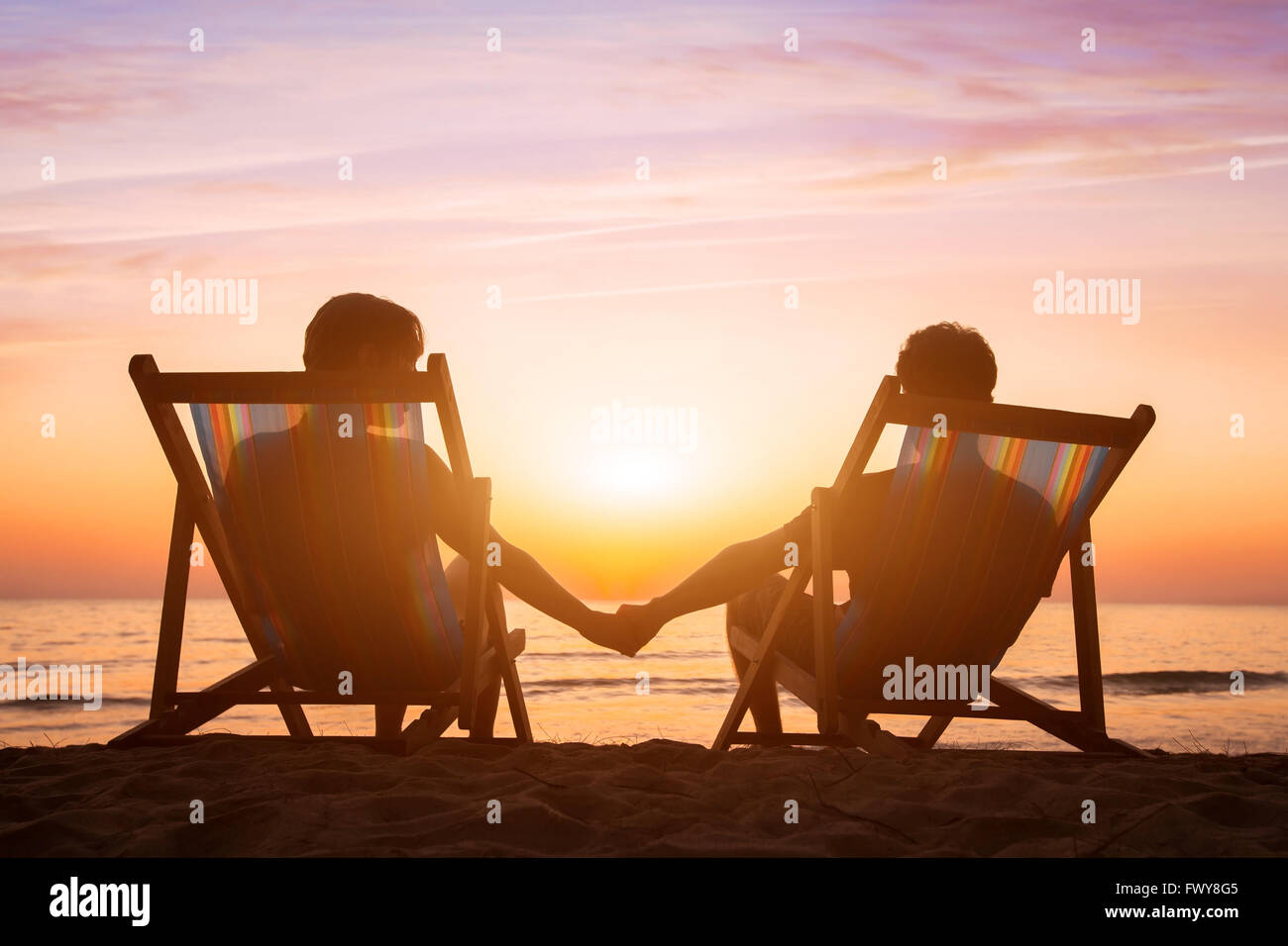 romantic love background, honeymoon, couple relaxing on the beach at sunset - Stock Image