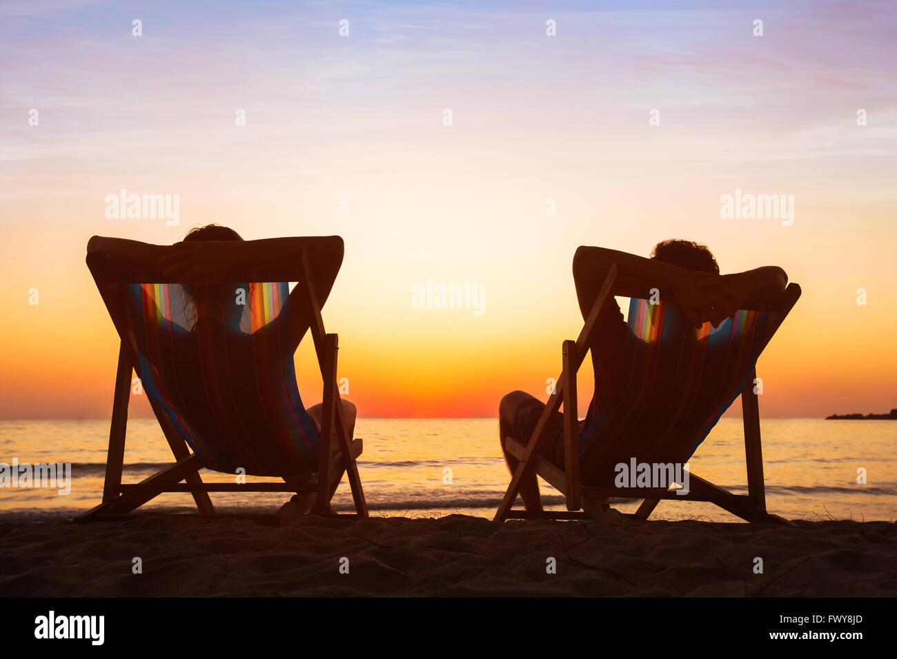 enjoy life concept, couple relaxing in beach hotel  at sunset, happy people on honeymoon, paradise travel destination Stock Photo