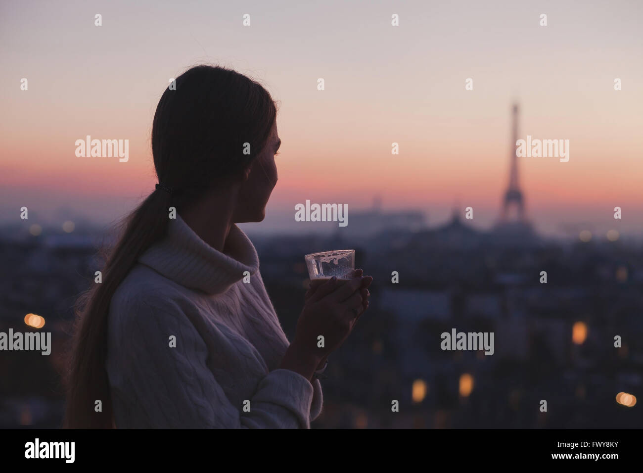 woman enjoying beautiful panoramic view of Paris with cup of coffee, cozy evening in cafe - Stock Image