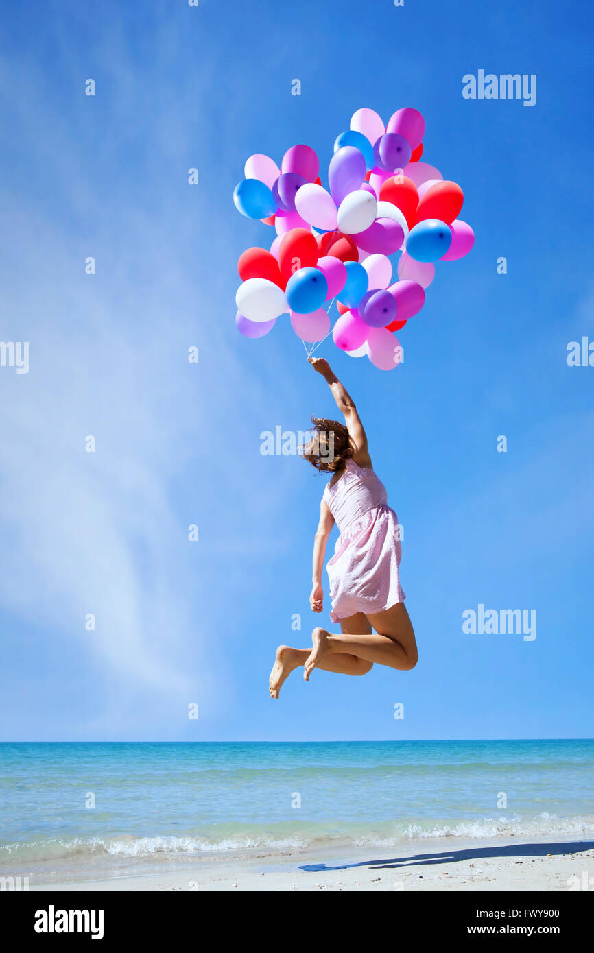 inspiration, happy people, woman flying with multicolored balloons in blue sky, creative concept - Stock Image
